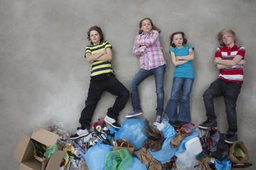 Kinder auf Stapel von Müll zeigen Ökologie-Symbol
