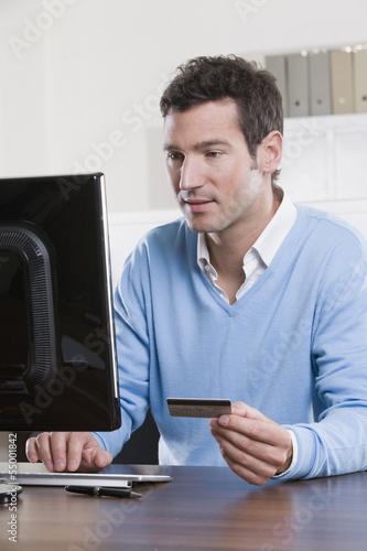 Deutschland, München, Geschäftsmann im Büro mit Kreditkarte