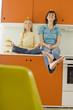 Mutter und Tochter in der Küche, Balancieren Orange auf dem Kopf