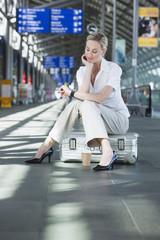 Deutschland, Leipzig-Halle, Junge Frau im Flughafen Abflughalle, sitzt auf Koffer