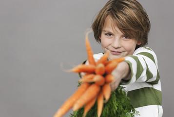 Junge hält ein Bündel Karotten