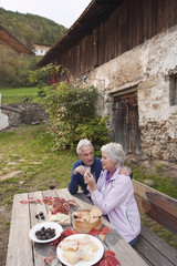 Italien, Südtirol, Älteres Paar mit Snacks in Berghütte
