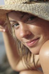 Italien, Sardinien, Junge Frau am Strand mit Strohhut