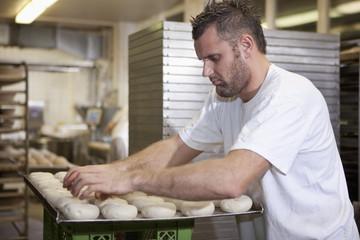 Deutschland, Bayern, München,Bäcker legt Brotteig auf Backblech
