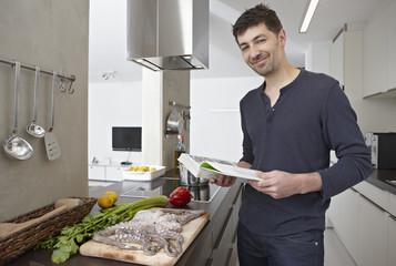 Deutschland, Köln, Mann mit Kochbuch in der Küche