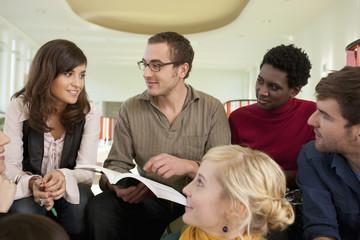 Deutschland, Leipzig, Gruppe von Studenten sitzt zusammen,sie lächeln