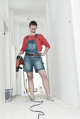 Deutschland, Köln, Junge Frau mit Bohrmaschine für die Renovierung im Korridor