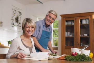 Deutschland, Kratzeburg, älteres Paar kocht mit Kochbuch