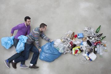 Männer kippen Müllsack aus