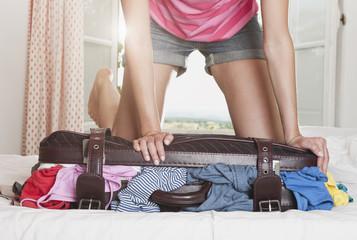 Italien, Toskana, Junge Frau schiebt Koffer im Hotelzimmer