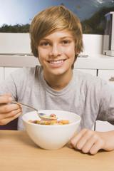 Teenager  mit Müsli zum Frühstück