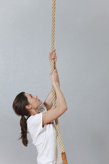 Deutschland, Berlin, Junge Frau an einem Kletterseil in der Turnhalle