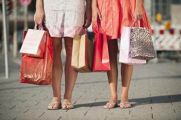 Deutschland, München, Karlsplatz, Junge Frauen warten auf Fußweg mit Einkaufstüten