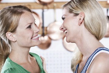 Italien, Toskana, Magliano, Zwei junge Frauen in der Küche, Lächeln, Nahaufnahme