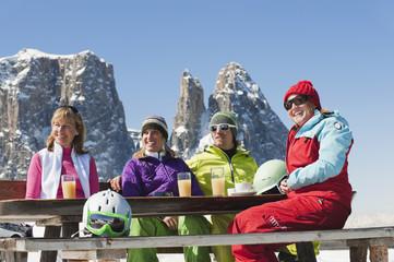 Italien, Trentino-Alto Adige, Südtirol, Bozen, Seiser Alm, Menschen sitzen auf der Bank mit Skiausrüstung und Getränken