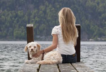 Österreich, Teenager-Mädchen mit Hund am Steg