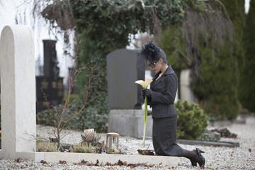 Deutschland, Bayern, Junge Frau besucht einen Grabstein auf dem Friedhof