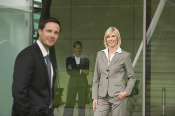 Deutschland, Unternehmerin, die Hände in der Tasche, mit Kollegen