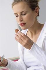 Frau isst Brezel, die Augen geschlossen