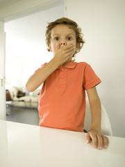 Junge, der seinen Mund mit den Händen zudeckt