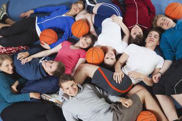 Deutschland, Berlin, Jugendliche liegen in einer Turnhalle