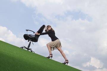 Deutschland, Bayern, München, Geschäftsfrau schiebt Stuhl auf dem Rasen