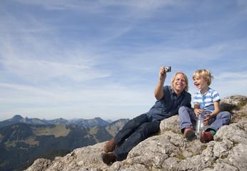 Deutschland, Bayern, Vater und Sohn machen Fotos auf Berggipfel
