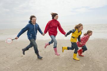 Deutschland, St. Peter-Ording, Nordsee, Familie hält zusammen und läuft am Strand