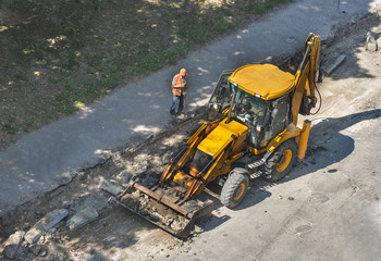 tractor performs road works to repair pavement