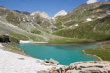 Lac blanc avec neige-névé, rochers et sommets