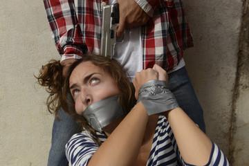 Gang member threatening kidnapped woman with gun