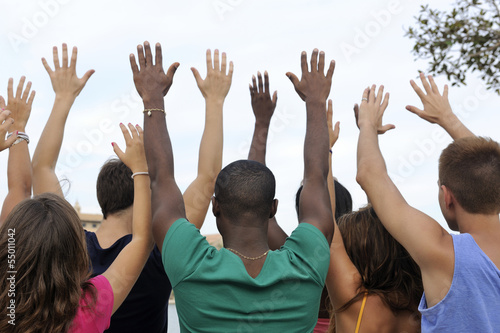 Diverse group raising hands