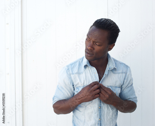 Portrait of a young black man adjusting shirt button outdoors