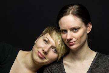 Lesbian couple posing against black background, horizontal