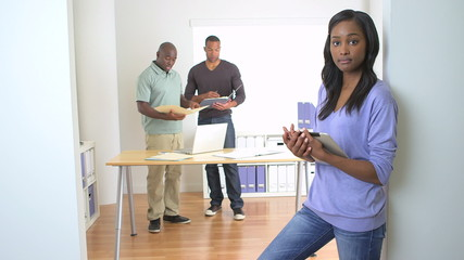 Confident black businesswoman standing with tablet