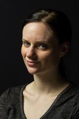 Young woman smiling at camera, vertical