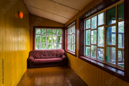 Empty spacious veranda with windows and a sofa