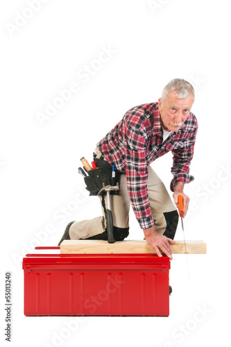 Senior manual worker sawing