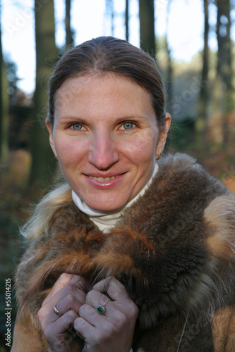 Portrait of young woman in fur coat in autumn or winter