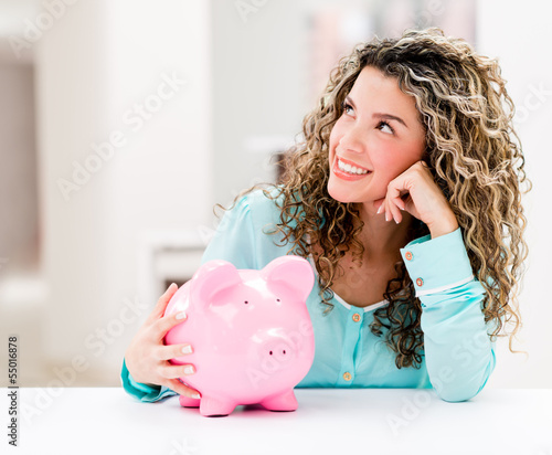 Thoughtful woman with a piggybank