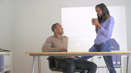 Two black co-workers talking in the office