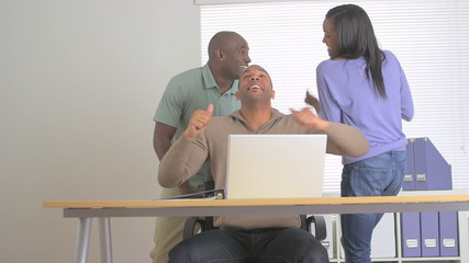 Black co-workers dancing in the office