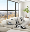White couch against huge windows with landscape view