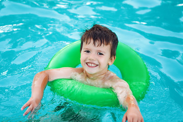 Happy young boy in pool with saver