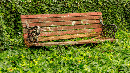 Vintage park bench with red peeling paint