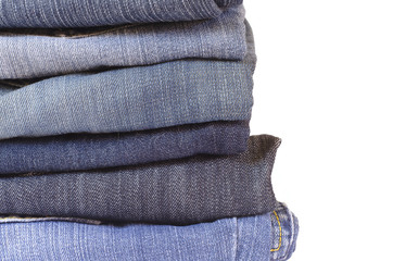 close up stack of folded jeans on white background