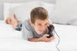 Little boy lying on bed playing video games