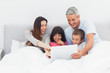 Family lying in bed using their laptop