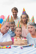 Cheeful family watching girl blowing out candles at birthday par