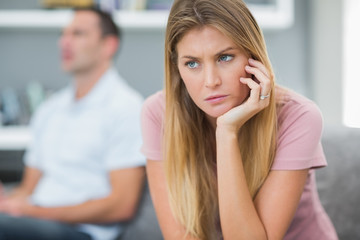 Sad woman thinking on couch after fight with husband